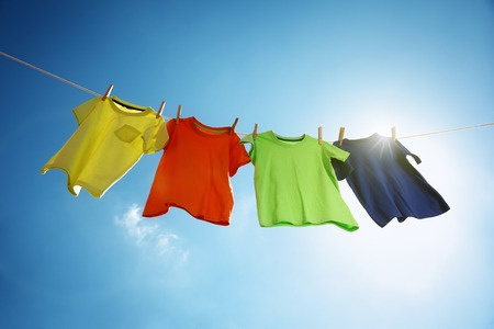38970372 - t-shirts hanging on a clothesline in front of blue sky and sun